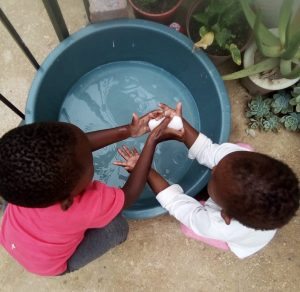 Diepsloot girl helping her neighbour wash hands during Covid19 lockdown